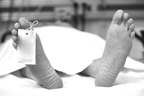 Close up of dead man's feet with toe tag reading Snuffed